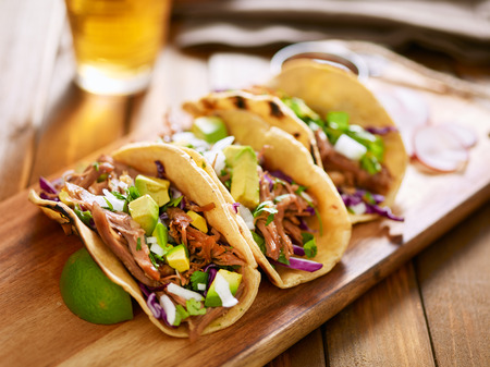 cilantro: three  pork carnitas street tacos in yellow corn tortilla with avocado, onion, cilantro and cabbage