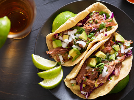 tasty pork street tacos with onion, cilantro, avocado, and red cabbage