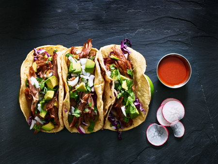 three mexican pork carnitas tacos flat lay composition Stockfoto