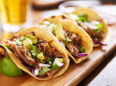 tortilla de maiz: tres tacos de carnitas de cerdo en la calle tortilla de maíz amarillo con el aguacate, la cebolla, el cilantro y la col Foto de archivo