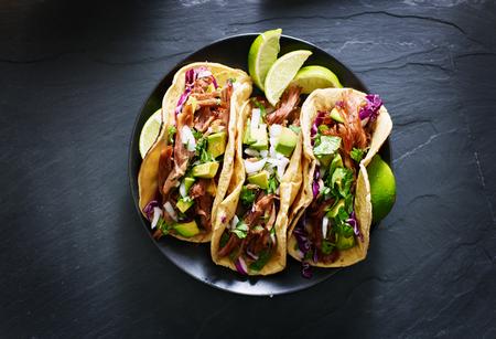Tacos callejeros mexicanos composición plana con carnitas de cerdo, aguacate, cebolla, cilantro y repollo rojo Foto de archivo