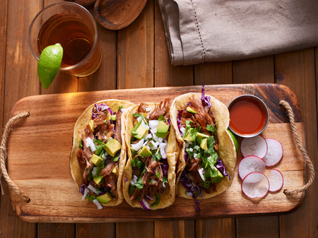 authentic: mexican pork carnitas tacos with beer on wooden tray and radish garnish.