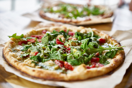 gourmet pizza: authentic gourmet pizza with fresh arugula, pesto and chicken Stock Photo