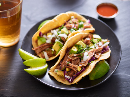 mexican carnita street tacos with beer on slate table setting