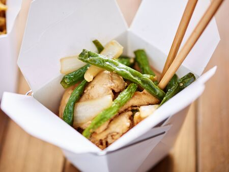 take out: eating chinese take out from container with chopsticks