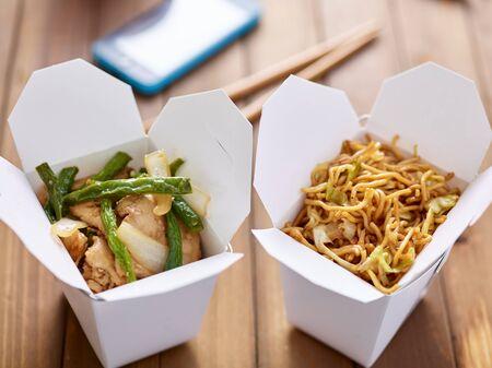 chinese prendre de la nourriture dans des boîtes de près avec un téléphone mobile en arrière-plan
