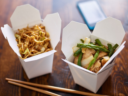 take out: chinese take out in boxes with chopsticks and phone in background