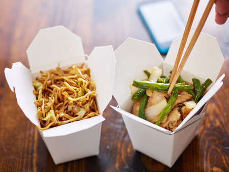 eating chicken and greenbeans out of chinese take out box with chopsticks