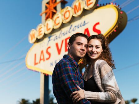 las vegas sign: happy couple posing in front of welcome to las vegas sign together
