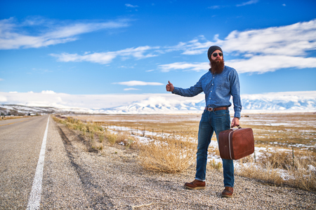 hobo: bearded hitch hiker thumbing for a ride on an empty nevada road Stock Photo