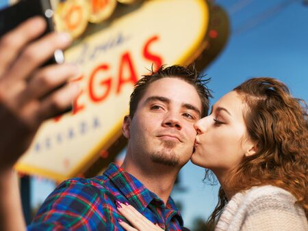 affections: happy couple take selfie in front of the welcome to las vegas sign