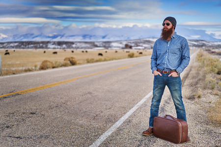 bearded traveling guy waiting along side empty american road in nevada