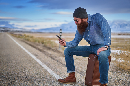 hobo: bearded hitch hiker sitting on suit case using smart phone