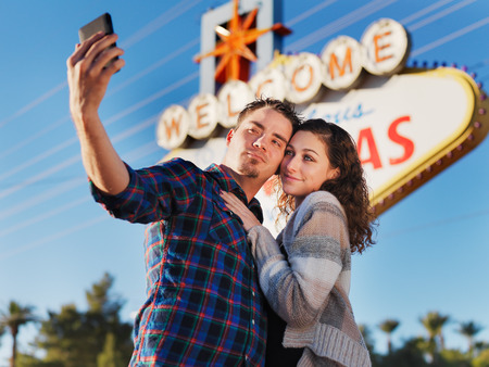 las vegas sign: couple in front of las vegas sign taking selfie with smartphone