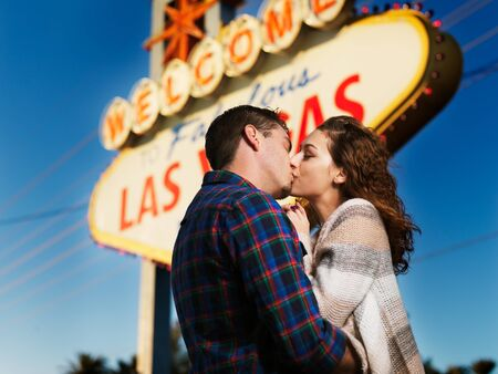 las vegas sign: romantic couple kissing in front of the welcome to las vegas sign Stock Photo