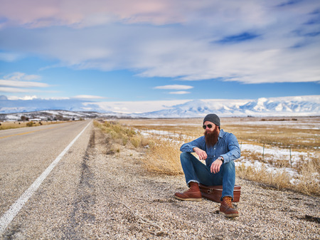 bearded traveler wiating along side road in nevada Stock Photo
