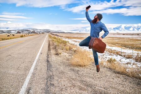 hitch: happy hitch hiker with beard and smart phone jumping for joy beside empty road in nevada Stock Photo