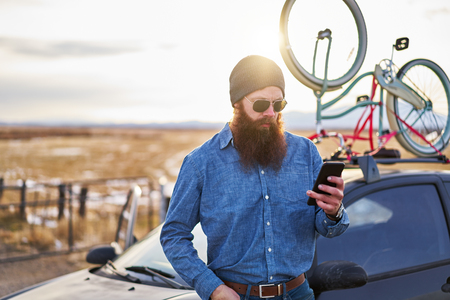 bearded traveler using smart phone in front of car with bike rack on road trip in nevada