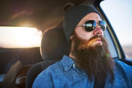 persona viajando: hombre de la barba en viaje por carretera que conduce el coche con gafas de sol