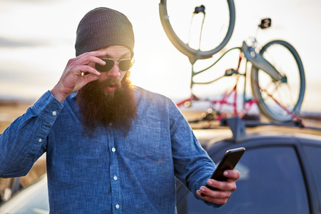 bearded traveler in front of car with bike rack making surprised expression when using smart phone Imagens