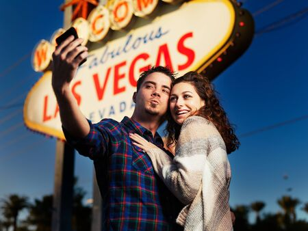 couple lit: couple taking selfies in front of lit up las vegas sign at night