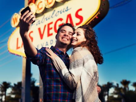 smiling happy tourist couple in front of lit up las vegas sign taking selfie