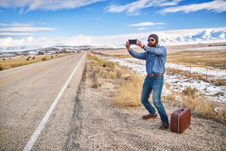 bearded hipster hitch hiker taking selfie beside empty road in nevada Stock Photo