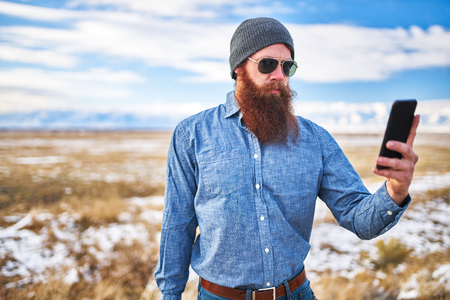 hitch: bearded hitch hiker using smartphone to look up directions