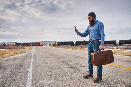 hitch: lost bearded hitch hiker with smart phone looking for directions on desolate nevada road Stock Photo