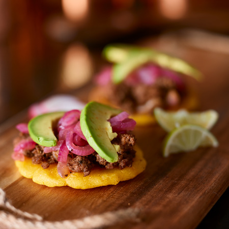 colombian food: beef arepas with avocado and pickled onion