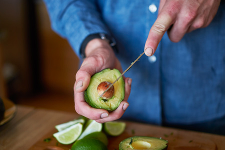 man cutting avocado to use in making guacamole Фото со стока