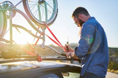 strapping: man strapping down bikes on bike rack Stock Photo