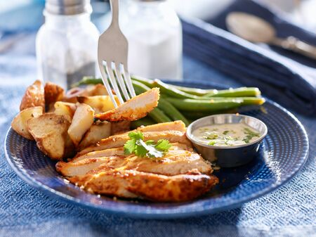greenbeans: eating baked seasoned chicken with fork