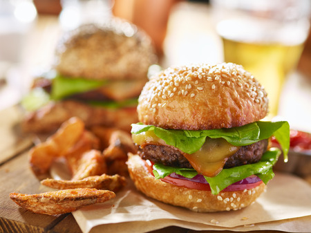 tasty cheese burgers with fries and beer in background Stock Photo