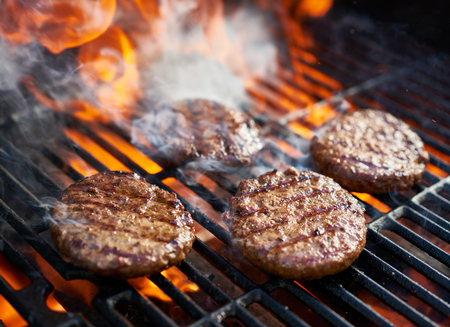 cooking burgers on hot grill with flames Archivio Fotografico