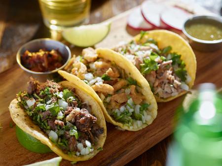 Tacos di strada messicani con barbacoa, carnitas e Chicharrón Archivio Fotografico - 67052815