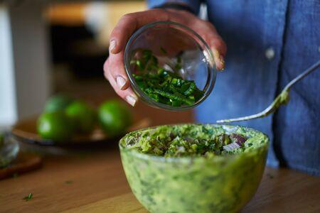 adding: adding jalapenos to guacamole Stock Photo