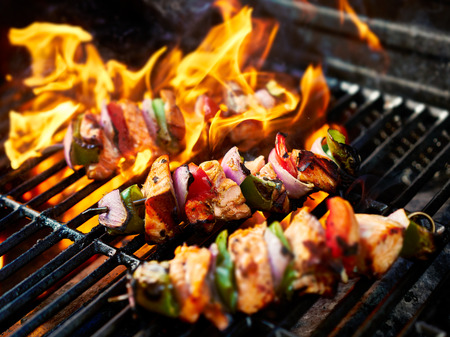 grilling chicken kabobs on flaming grill Фото со стока