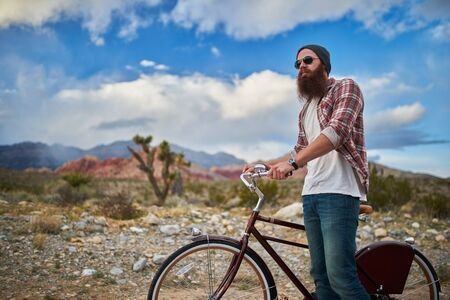 stopped: man stopped on bike in nevada desert beside redrock Stock Photo