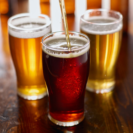 pouring beer into glass with assorted types of beers in background Stock Photo