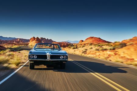 사막을 통해 빈티지 자동차 운전 남자 스톡 콘텐츠