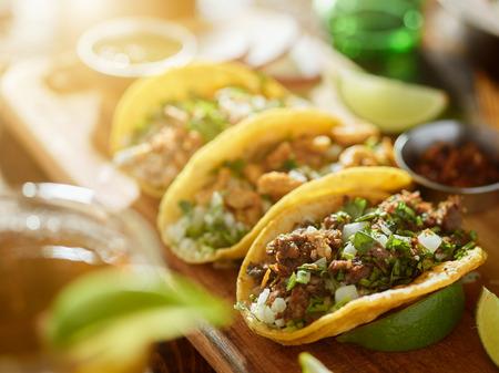 tortilla de maiz: tres tipos de tacos de la calle mexicanos con Barbacoa, carnitas y Chicharrón, tiro con reflejo en la lente y el foco selectivo Foto de archivo