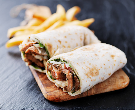 greek gyro wrap cut in half and served with fries Imagens - 71188048