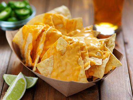 nachos and cheese in tray with beer