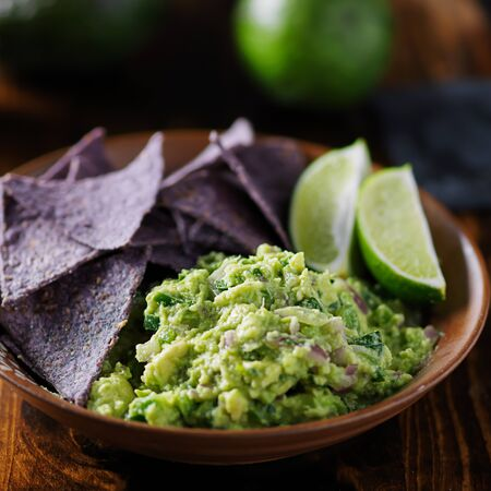 colorful blue corn tortilla chips with fresh mexican guacamole and lime wedges Stock Photo