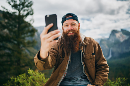 cool bearded man taking selfie photo with smartphone infront of yosemite