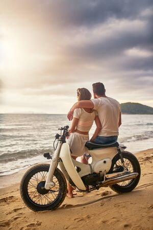 romantic couple sitting on vintage bike watching sunset at koh samui thailand