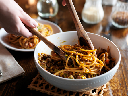 europe: serving spaghetti with wooden spoons out of bowl