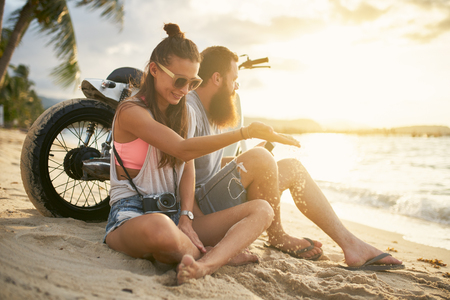 freedom: romantic couple couple with motorbike in thailand watching sunset Stock Photo