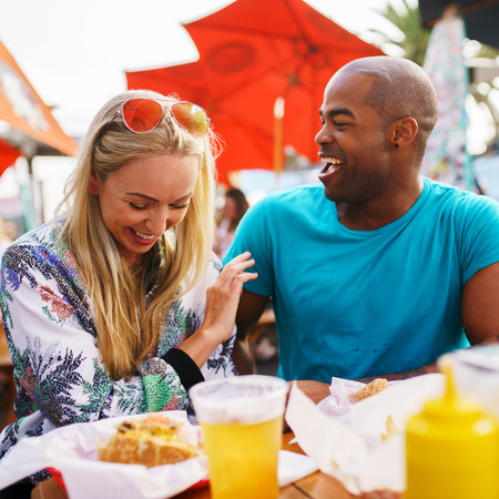 african american woman: playful couple eating at outdoor restaurant with burgers and beer
